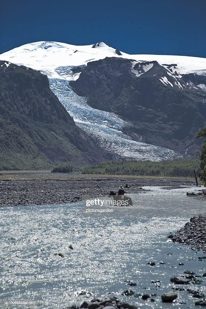 Man riding on horse through river, snowcapped mountains in background : Foto stock