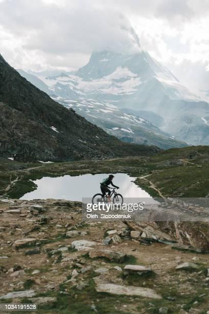 mann reitet auf mountainbike in der nähe des sees mit blick auf matterhorn - pedalantrieb stock-fotos und bilder