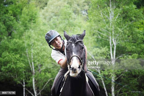 man riding on the horse and stroking it in the ranch in the rain - 乗馬 ストックフォトと画像
