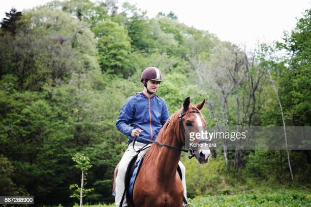 man riding on the horse in the ranch in the rain - horseback riding stock pictures, royalty-free photos & images
