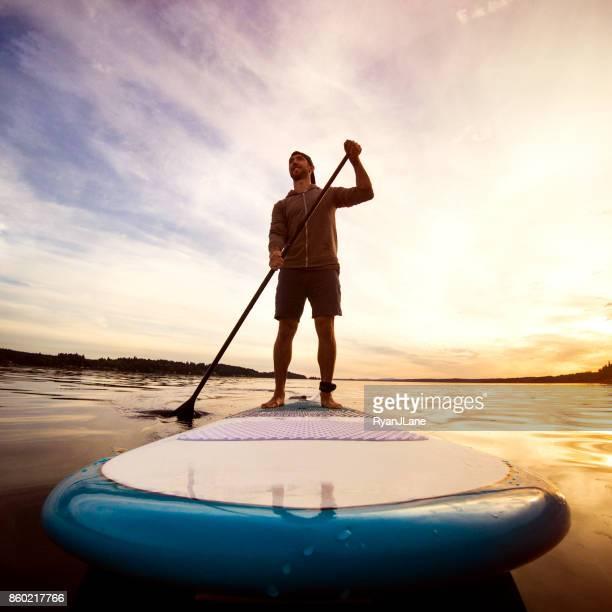 Hombre caballo Paddleboard en Puget Sound al atardecer