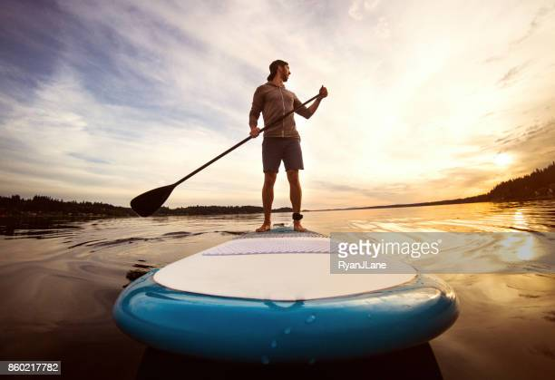 man riding paddleboard on puget sound at sunset - wide angle stock pictures, royalty-free photos & images