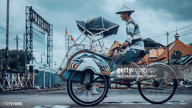 man riding pedicab on road in city - yogyakarta stock pictures, royalty-free photos & images