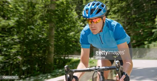 man riding road bike on mountain road - road cycling stock pictures, royalty-free photos & images