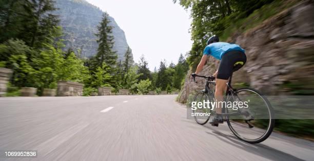 bicicleta de carretera de montar a caballo de hombre en carretera de montaña - contrarreloj evento deportivo fotografías e imágenes de stock