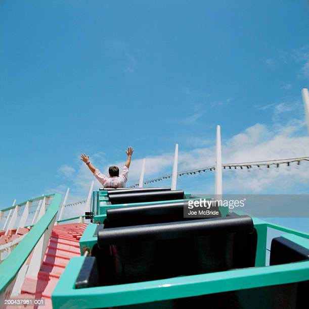 man riding rollercoaster, rear view - amusement park ride stock pictures, royalty-free photos & images