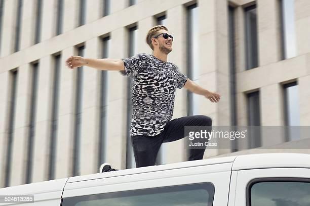 man riding the top of a car through the city