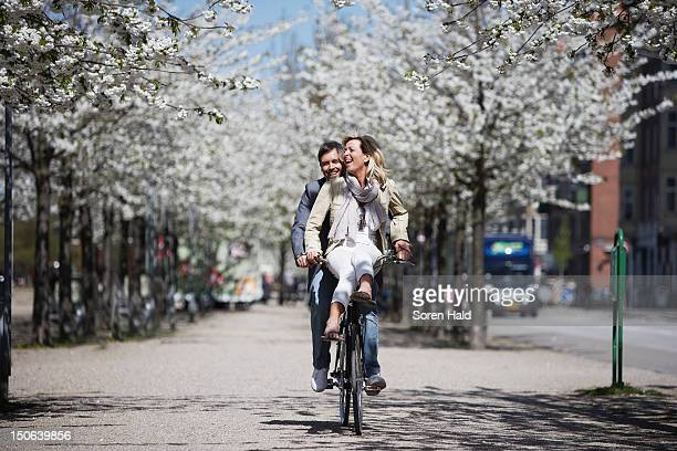 man riding with girlfriend on bicycle - weekend activiteiten stockfoto's en -beelden