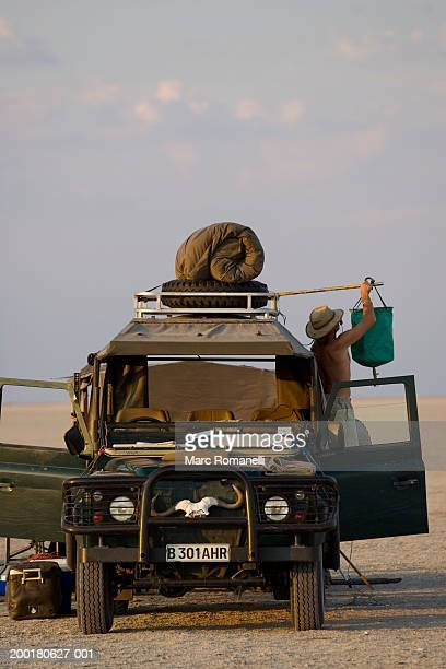 man rigging solar shower to safari vehicle - moremi wildlife reserve stock photos and pictures