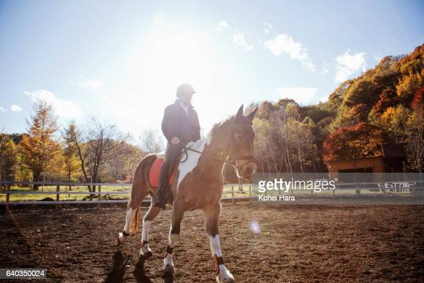 Man rinding on horse in pasture