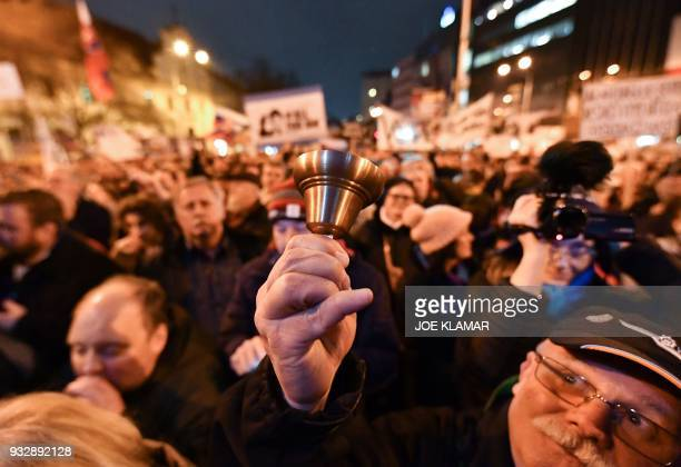 TOPSHOT A man rings a bell as he takes part in a rally near the Slovak National Uprising square under the slogan For a Decent Slovakia against...