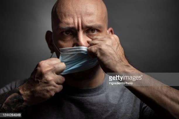 de mens scheurt een beschermend masker van zijn gezicht. - woede stockfoto's en -beelden