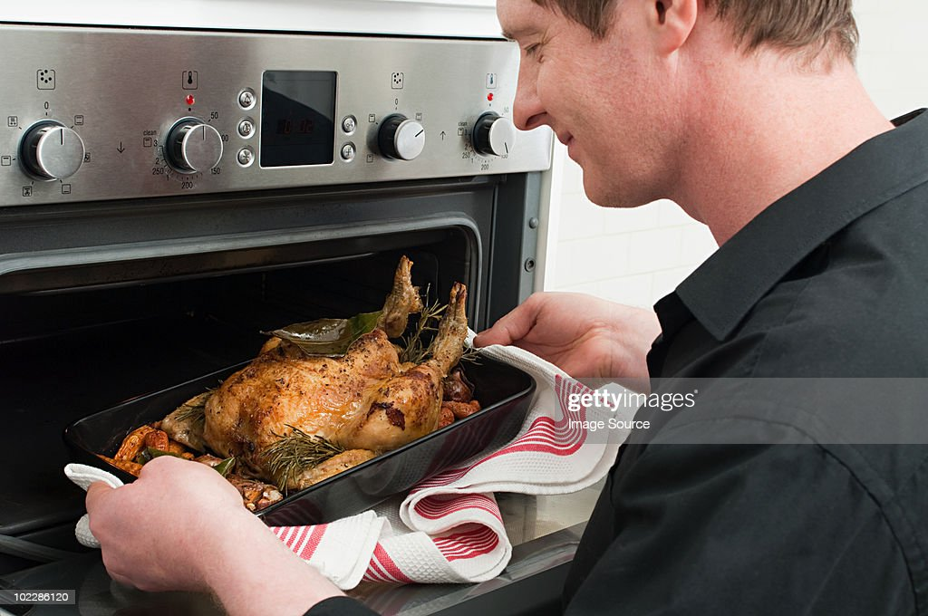 Man roasting chicken in oven : Stock Photo