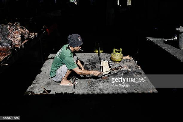 A man roasts a bat at Langowan traditional market on August 9 2014 in Langowan North Sulawesi The Langowan traditional market is famous for selling a...