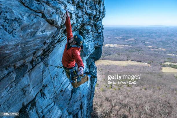 man rock climbing against landscape - mountaineering stock pictures, royalty-free photos & images