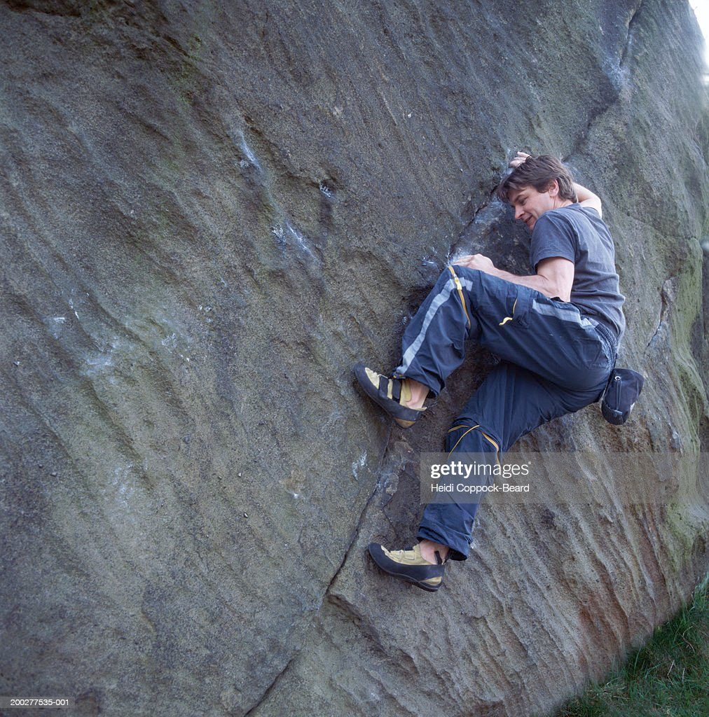 Man rock climbing along crack in rock wall, low angle view : Stock Photo