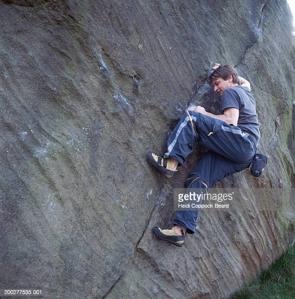 man rock climbing along crack in rock wall, low angle view - heidi coppock beard fotografías e imágenes de stock