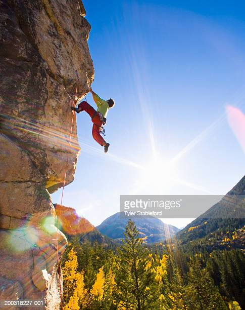 Man rock climbing, dangling from overhang, low angle view (wide angle)