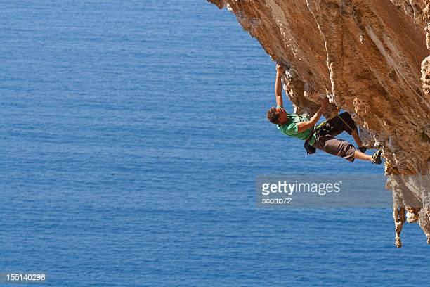 man rock climbing near an ocean - rock overhang stock photos and pictures