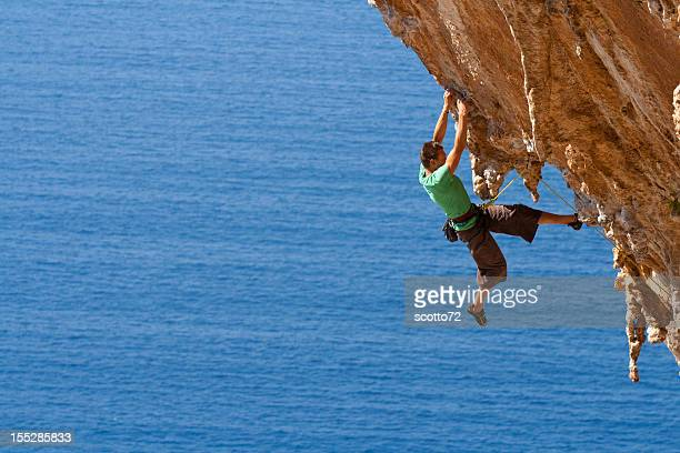 a man rock climbing on a large steep cliff near the ocean - rock overhang stock photos and pictures