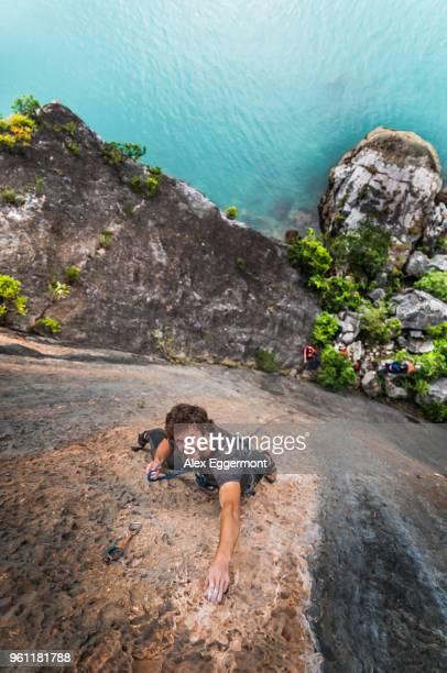 man rock climbing on limestone rock, overhead view, ha long bay, vietnam - extra long ストックフォトと画像