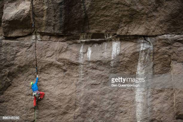 a man rock climbing up a large wall - rock wall stock pictures, royalty-free photos & images