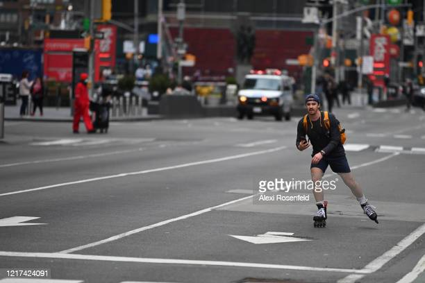 A man rollerblades down an empty 7th Avenue in Times Square amid the coronavirus pandemic on April 05 2020 in New York City COVID19 has spread to...