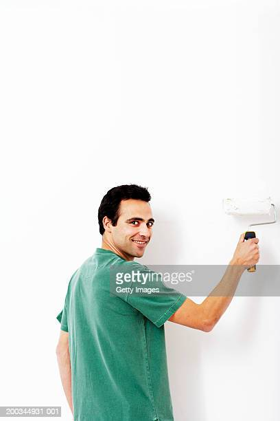 Man rolling paint on wall, smiling, portrait