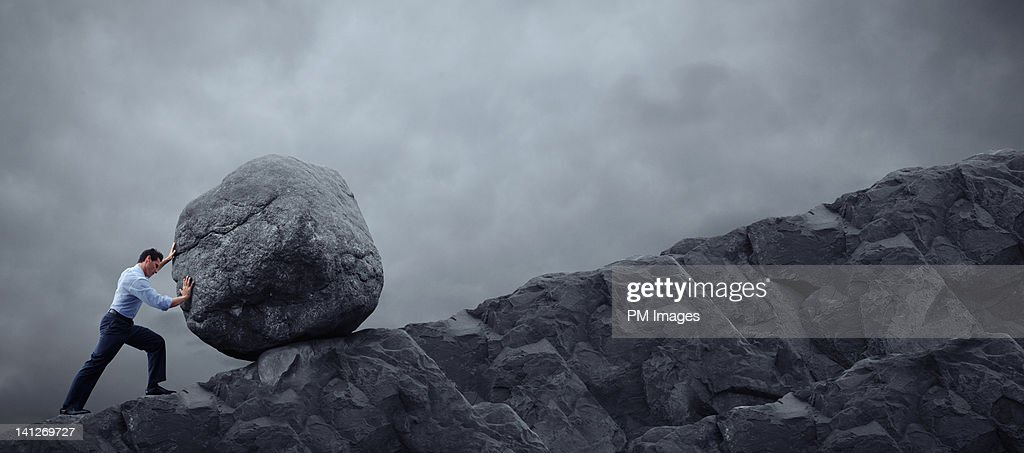 Man rolling rock up hill : Stock Photo