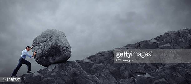 man rolling rock up hill - struggle stock pictures, royalty-free photos & images