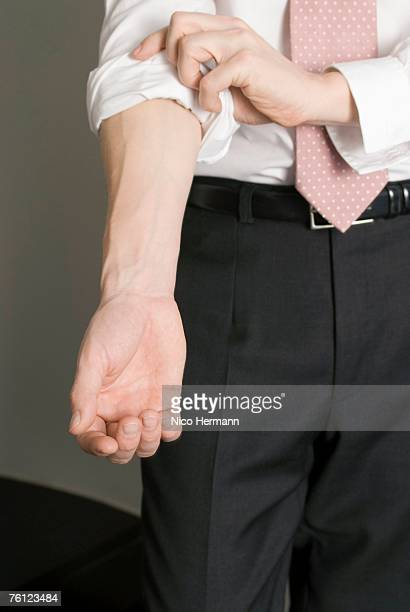 Businessman rolling up sleeve, close-up, mid section