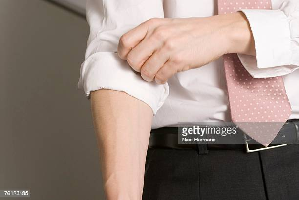 Businessman rolling up his sleeve, close-up