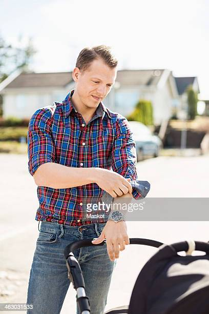 man rolling up shirt sleeve while looking at baby carriage on street - long sleeved stock pictures, royalty-free photos & images