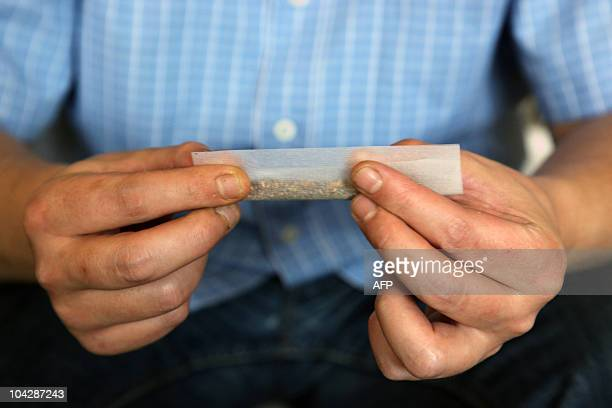 A man rolls a hashish joint at his home in Cairo on April 4 2010 Egypt's market for the illegal drug hashish is going through a shortage that is...