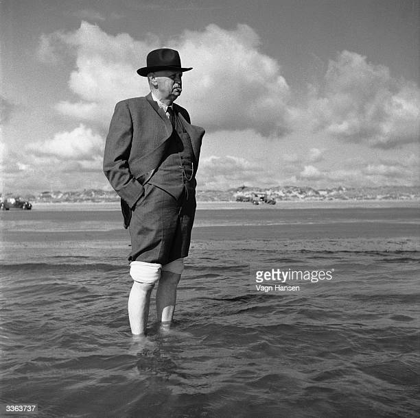 A man rolls up the legs of his suit paddles into the water to turn his back on the world and stare out to sea