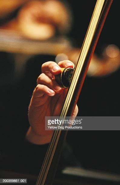Man rosining cello bow, close-up