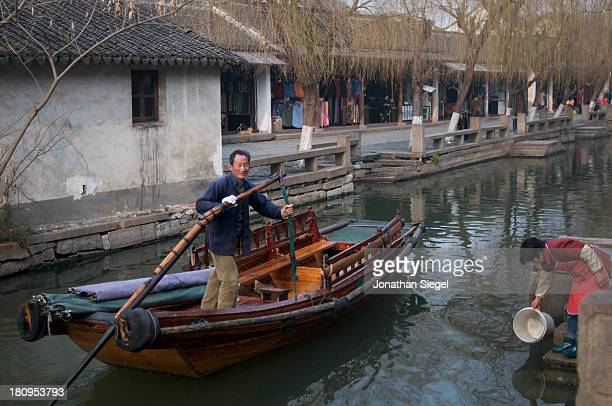 CONTENT] A man rowing a boat stops to smile in the beautiful river town of Zhouzhuang a town in the Jiangsu province of China
