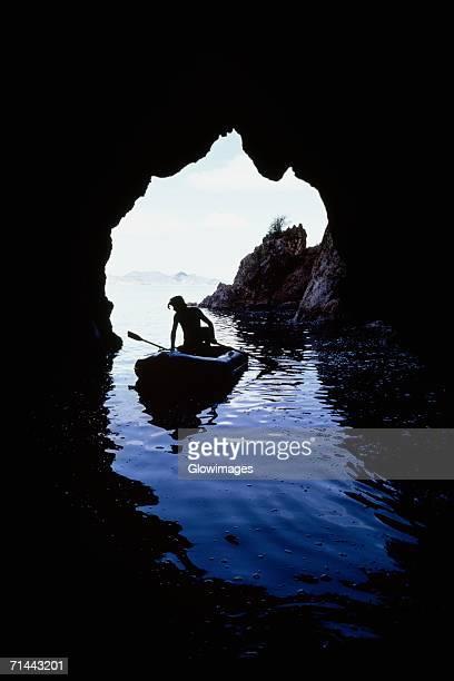 A man rowing a canoe seen through the cave, Treasure Island, Virgin Islands