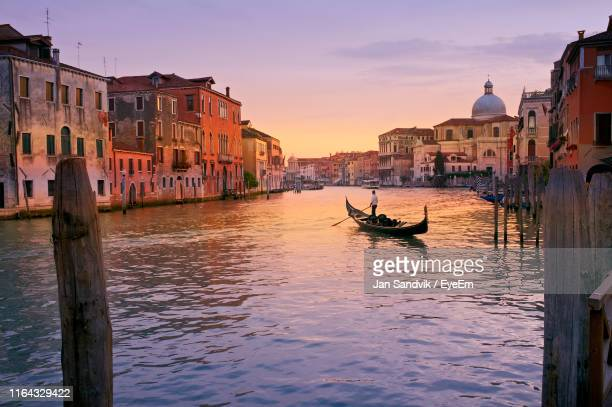 man rowing boat in canal by buildings - venezia foto e immagini stock