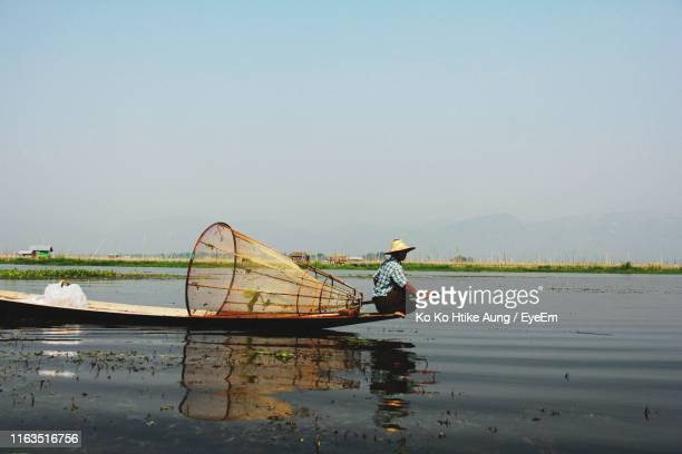 man rowing boat in lake against clear sky - ko ko htike aung stock pictures, royalty-free photos & images
