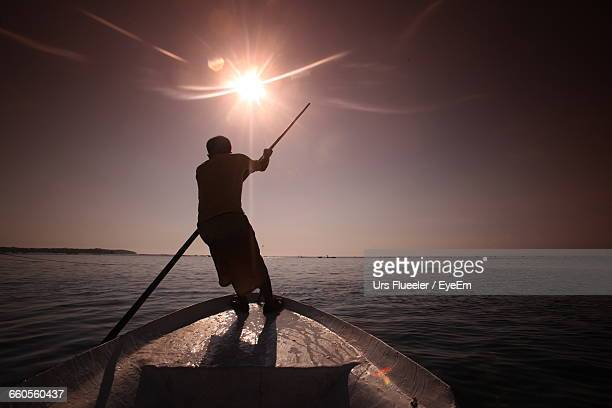 Man Rowing Boat In River Against Sky On Sunny Day
