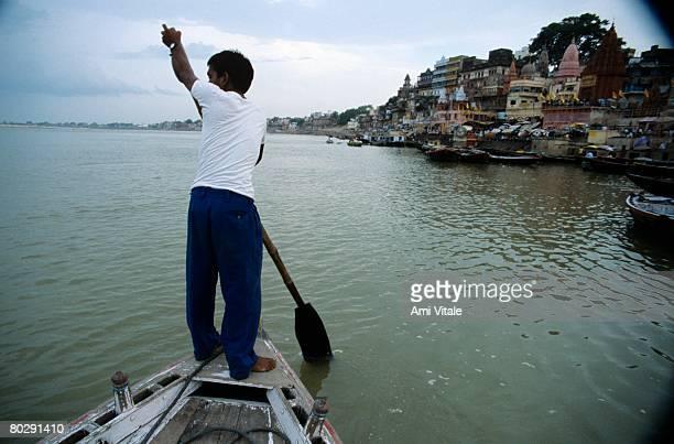 Man rowing boat on Ganges River, Varanasi, India