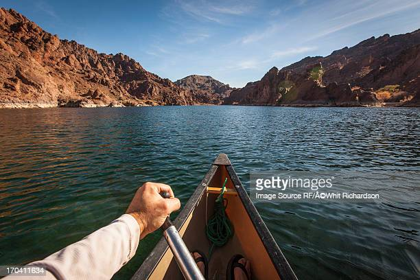 man rowing canoe on still rural lake - boulder city stock photos and pictures