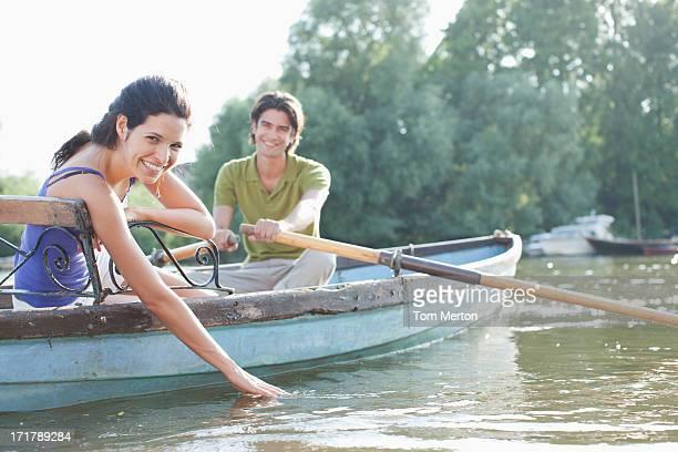 Man rowing girlfriend in rowboat on lake