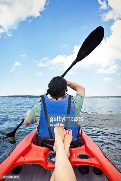 Man Rowing Kayak While Woman Relaxes