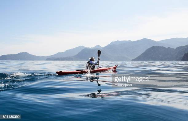 a man rowing on a sea kayak - sea kayaking stock pictures, royalty-free photos & images
