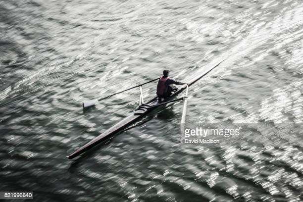 man rowing on lake - rowing stock pictures, royalty-free photos & images