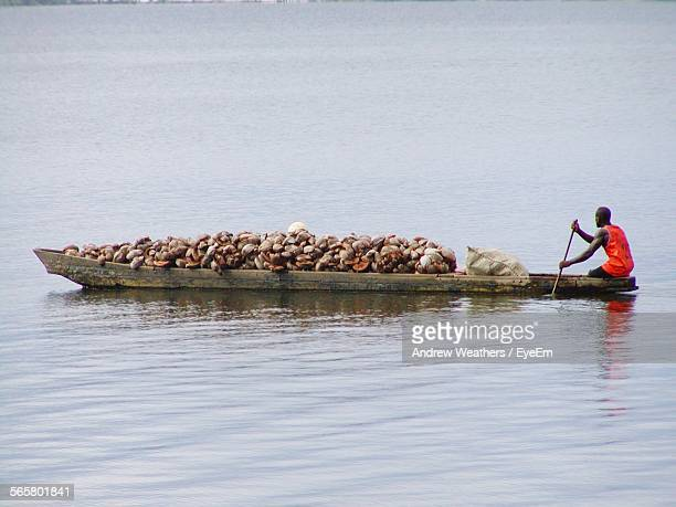 man rowing rowboat in river - côte d'ivoire stock pictures, royalty-free photos & images