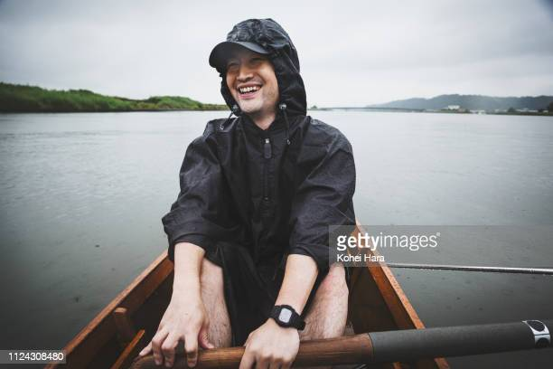 Man rowing scull in the river on rainy days