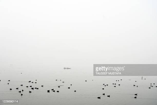 Man rows a boat amid dense fog in the Dal Lake in Srinagar on November 12, 2020.